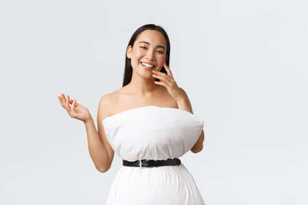 Beauty, fashion and social media concept. Pretty happy asian woman laughing and show-off her new outfit made of pillow and belt, posing in pillow dress over white background