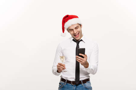 Christmas Concept - Handsome Business man talking on phone and holding glass of champange celebrating Chirstmas and New year. Stock Photo