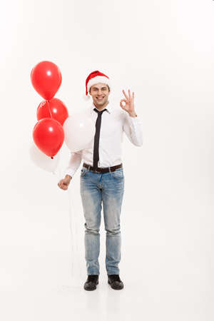 Christmas Concept - Handsome happy Business man walking with red balloon celebrate merry christmas and happy new year wear santa hat.