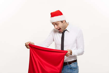 Christmas Concept - Handsome Business man celebrate merry christmas and happy new year wear santa hat with Santa red big bag.