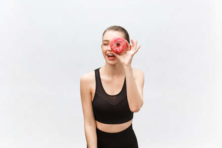 Young beautiful sporty woman in a black undershirt poses and smiles isolated on white background. Girl poses with donut in hands. I have applied donut to the eye Standard-Bild