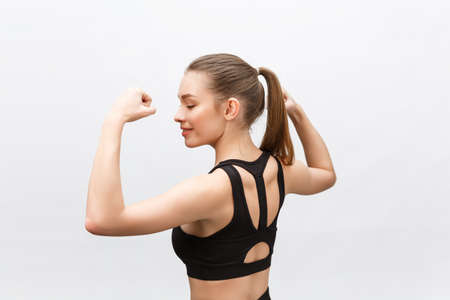 Waist up shot of sporty woman raises hand to show her muscles, feels confident in victory, looks stong and independent, smiles positively, stands against grey background. Sport concept Imagens