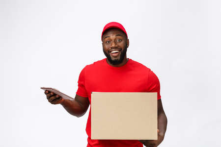 Delivery Concept - Portrait of Handsome African American delivery man or courier showing a confirmation document form to sign. Isolated on Grey studio Background. Copy Space
