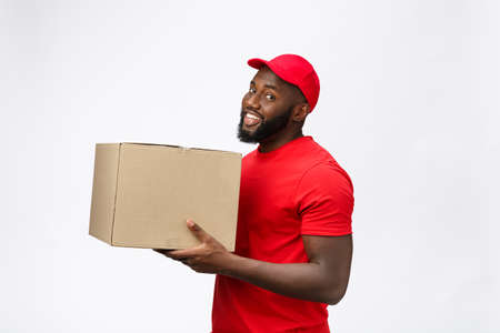 Delivery Concept - Side view Portrait of Happy African American delivery man in red cloth holding a box package. Isolated on Grey Background. Copy Space Banque d'images
