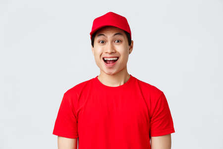 Delivery, contactless orders and shopping concept. Excited delivery guy in red uniform cap and t-shirt, courier smiling amused, look camera enthusiastic, advertise carrier service, grey background Zdjęcie Seryjne