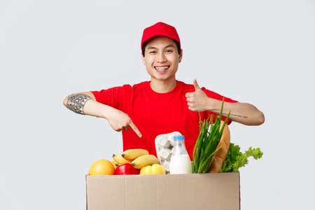 Online shopping, food delivery and internet stores concept. Smiling friendly courier in red t-shirt and cap, show thumb-up, point at order grocery package, point products, recommend carrier service