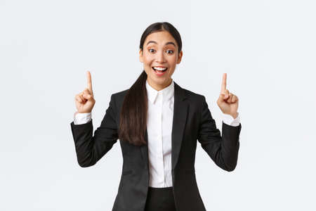 Excited smiling asian saleswoman in suit suggest great deal, pointing fingers up as telling details. Businesswoman making announcement and showing top banner, white background