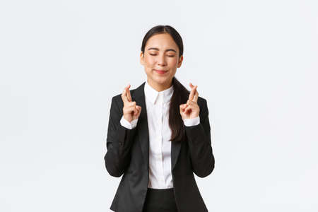 Hopeful optimistic businesswoman having faith in herself, believe dreams come true, cross fingers for good luck and close eyes as making wish, praying for relish, white background