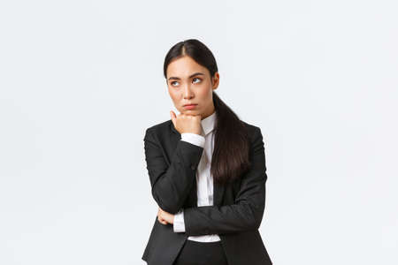Bored and annoyed female entrepreneur looking unamused away while sitting boring meeting, attend uninteresting office gathering, standing white background dying boredom