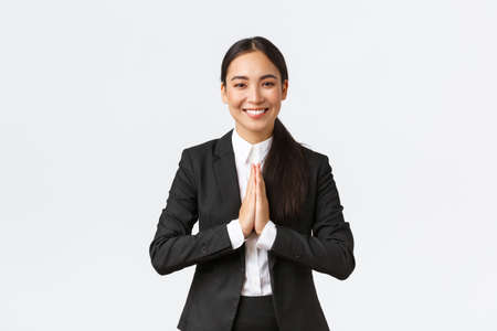 Hopeful glad asian businesswoman in black suit bowing politely and say namaste, greeting clients and smiling friendly. Thankful female manager thanking for help, being grateful, appreciate help