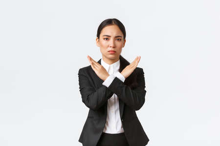 Serious-looking confident businesswoman in black suit showing cross gesture to forbid action, restrict, forbid or prohibit making any deals, stop working with client, white background. Time out