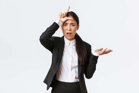 Bothered and annoyed asian businesswoman scolding employee for failure, showing loser gesture and raising hand in dismay, cant understand why so stupid, complaining over white background