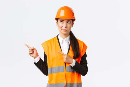 Building, construction and industrial concept. Indecisive asian female architect being unsure, wearing reflective clothing and helmer, smirk as pointing and looking upper left corner puzzled