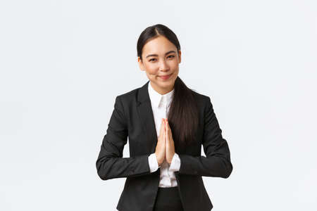 Friendly asian businesswoman hold hands together and bowing at business partners, greeting clients. Female entrepreneur say namaste and welcome customers, white background