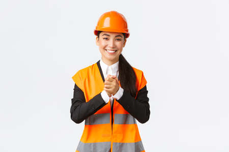 Thankful successful asian female architect greet investors or clients at construction area, wearing safety helmet and jacket, shaking clenched hands in appreciation, being grateful for trust