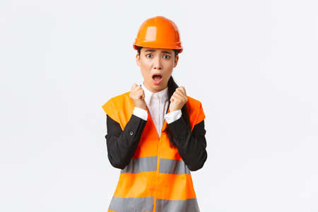 Scared asian female engineer in panic looking shocked and afraid, shivering from fear, wearing safety helmet and reflective jacket, feel concerned and alarmed as having problem at construction zone