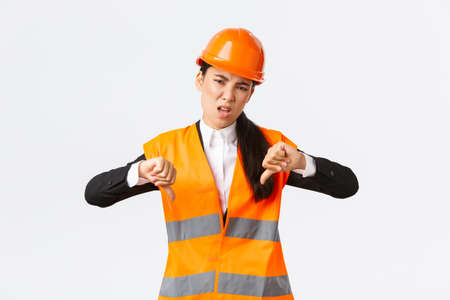 Disappointed and upset asian female chief engineer inspect bad work, showing thumbs-down disappointed, wear safety helmet and complaining weak awful work of architect, white background