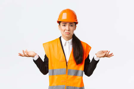 Upset and confused asian female engineer feeling complicated, raising hands sideways and shrugging, dont know why, have no idea, being clueless, pouting and being sad, white background