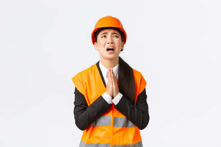 Desperate and reckless asian female construction manager, architect pleading god, wearing safety helmet, holding hands in pray, supplicating, asking god help, begging over white background