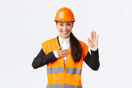Sincere, honest and confident asian female engineer at building area, making promise, give oath to clients, looking trustworthy, standing in safety helmet, telling truth, white background