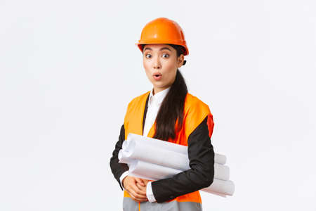 Surprised and excited asian female chief architect in safety helmet and reflective jacket, visit construction area with blueprint, looking amused, listening to interesting suggestion of manager