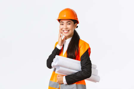 Smiling happy asian female architect, construction manager in safety helmet and jacket, carry blueprints of building project and looking delighted, finish plan in time, standing white background