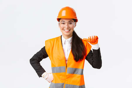 Professional and talented confident smiling asian female engineer, construction architect in safety helmet and glasses, pointing at herself proud, promote own abilities and skills, white background
