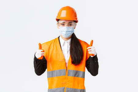 Covid-19 safety protocol at enterpise, construction and preventing virus concept. Confident female asian industrial worker, engineer in face mask and helmet showing thumbs-up, all good