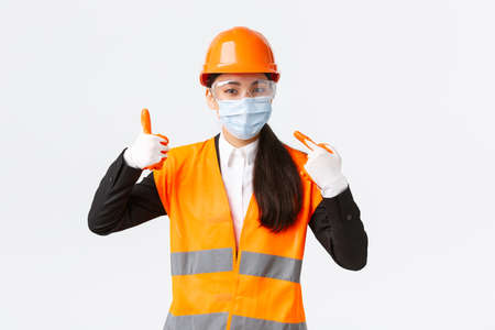 Covid-19 safety protocol at enterpise, construction and preventing virus concept. Asian female chief engineer telling wear face mask at work, pointing at hers and showing thumbs-up in approval