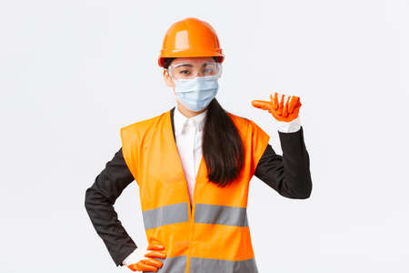 Covid-19 safety protocol at enterpise, construction and preventing virus concept. Confident asian female engineer in helmet and face mask pointing at herself, advertise personal assitance
