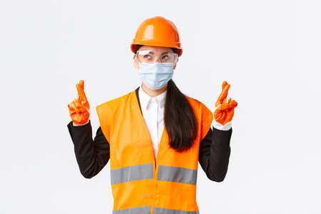 Covid-19 safety protocol at enterpise, construction and preventing virus concept. Hopeful optimistic asian female engineer in helmet and face mask making wish, looking left pleased, cross fingers Archivio Fotografico