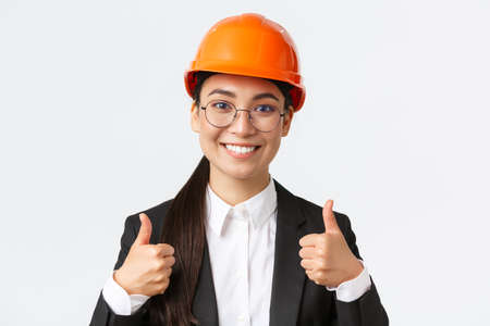 Close-up of professional pleased asian female chief engineer, architect in business suit and safety helmet showing thumbs-up in approval, give permission, recommend construction company