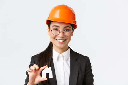 Close-up of happy asian female engingeer, real estate agent in helmet and business suit holding house miniature and smiling, architect working over renovation project, white background