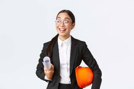 Hopeful and excited asian female architect looking around with fascination and amazement, holding blueprints and helmet, walking in construction area, standing in business suit over white background