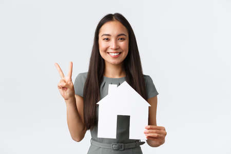 Insurance, loan, real estate and family concept. Smiling attractive asian woman selling or buying apartment, showing peace kawaii sign and paper house, saleswoman showing home, white background