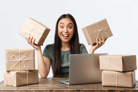 Small business owners, startup and e-commerce concept. Smiling asian businesswoman working from home managing online store via laptop, packing parcels for clients, checking info for shipping