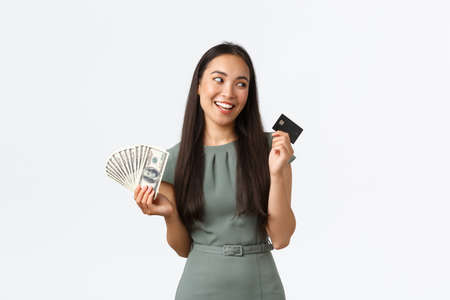 Small business owners, women entrepreneurs concept. Pleased asian woman prefer buying things and shopping with contactless payment, choosing credit card instead of cash, holding money