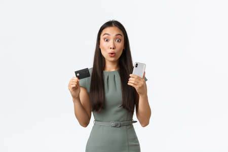 Small business owners, women entrepreneurs concept. Surprised and excited asian female buying online, looking impressed with discounts while holding credit card and smartphone to make order