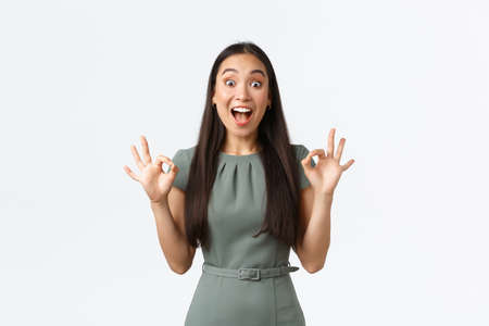 Small business owners, women entrepreneurs concept. Excited happy asian woman looking pleased and extremely thrilled, showing okay gesture and smiling astounded, white background