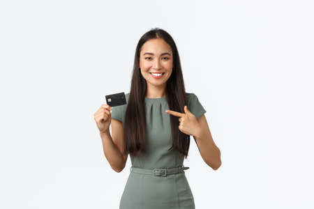 Small business owners, women entrepreneurs concept. Smiling attractive businesswoman, bank clerk in dress, pointing finger at credit card, promote new service, finance app, white background