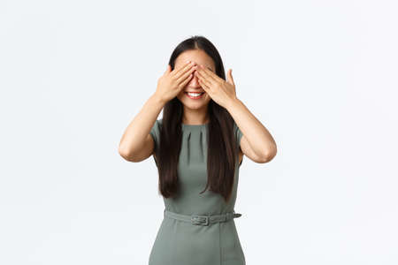 Small business owners, women entrepreneurs concept. Excited smiling pretty asian female in dress expecting surprise, shut eyes as awaiting for gift, standing hopeful over white background
