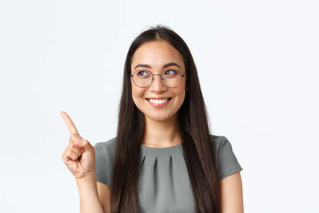 Small business owners, startup and e-commerce concept. Close-up of creative smiling female asian entrepreneur giving speech, making announcement, pointing finger upper left corner