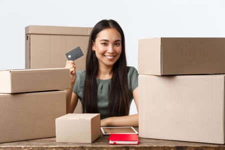 Small business owners, startup and e-commerce concept. Smiling asian businesswoman except credit cards while selling products online, packing orders in boxes, sitting office at home, white background