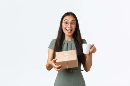 Excited happy asian woman drinking coffee and receive home delivery, holding box package with cheerful smile, finally receiving order from online shop, standing white background Stock fotó