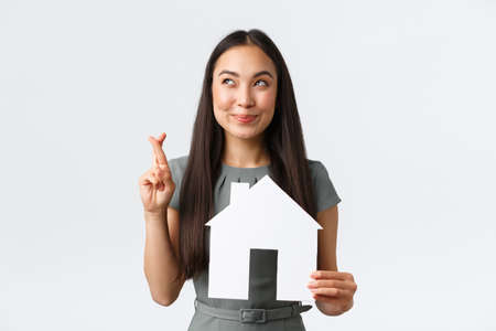 Insurance, loan, real estate and family concept. Hopeful and optimistic smiling asian woman cross fingers and smiling, dreaming of finding new home, holding paper house, making wish