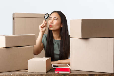 Small business owners, startup and e-commerce concept. Asian businesswoman looking through magnifying glass as searching for something while packing orders in boxes, work from home
