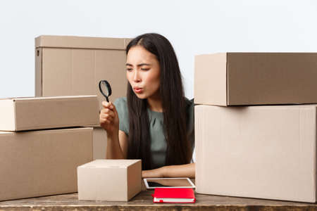 Small business owners, startup and e-commerce concept. Asian businesswoman looking serious at box with magnifying glass, studying parcel, ensure order shipping info correct, white background Archivio Fotografico