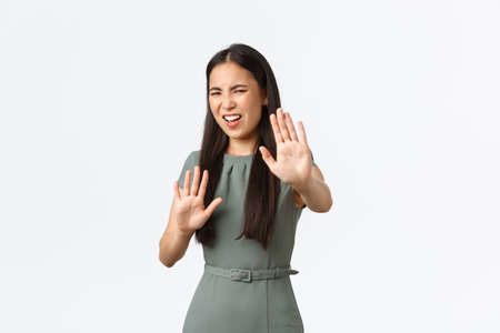 Small business owners, women entrepreneurs concept. Displeased and reluctant asian female in dress step back asking stay away, showing stop, rejection or refusal gesture, standing white background