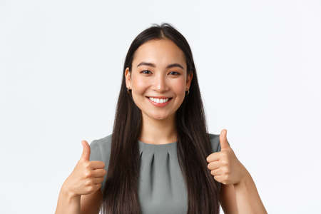 Close-up of satisfied and happy smiling asian businesswoman giving positive feedback, praise nice job, showing well done, great work gesture, thumbs-up pleased as standing white background