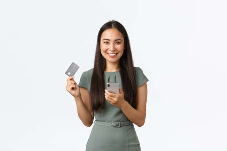 Small business owners, women entrepreneurs concept. Smiling attractive asian woman in dress making online purchase, buying tickets for work flight, holding mobile phone and credit card pleased